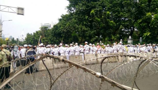 Laskar Front Pembela Islam membentuk barisan untuk mengamankan massa aksi damai 505 yang berkumpul di depan Gedung Kementerian Dalam Negeri, Jakarta, Jumat, 5 Mei 2017. (Foto : TEMPO)